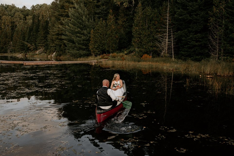 bride and groom canoeing in a lake
