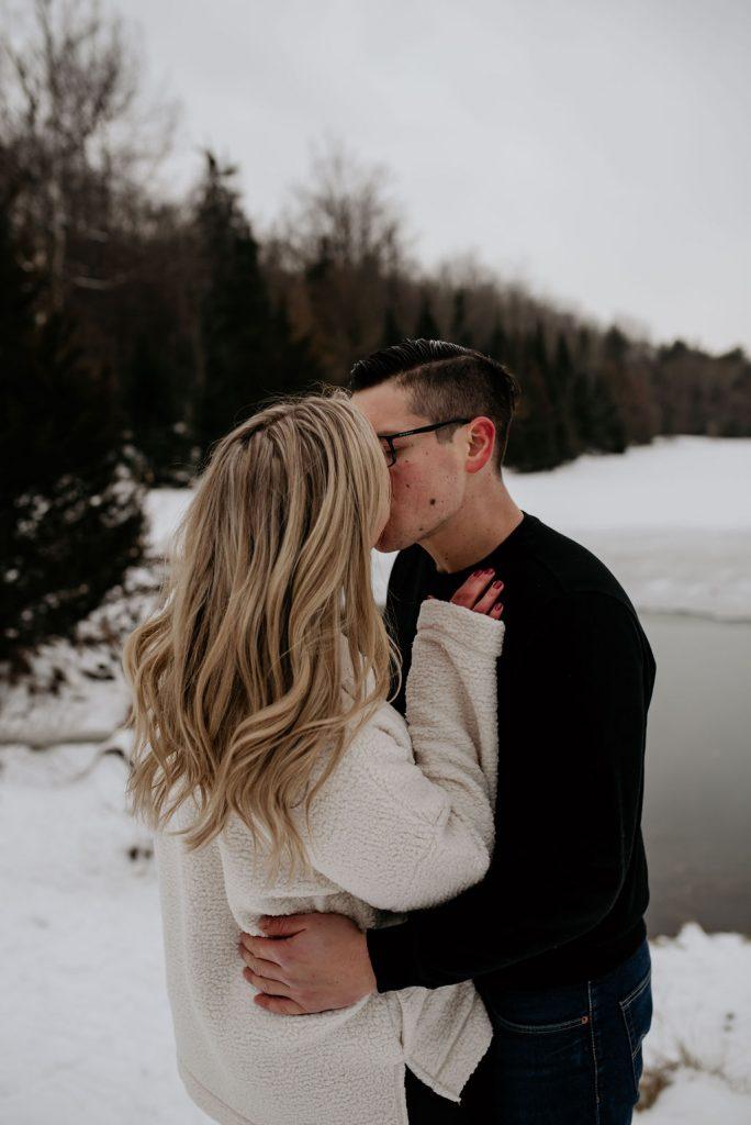couple kissing beside lake in winter