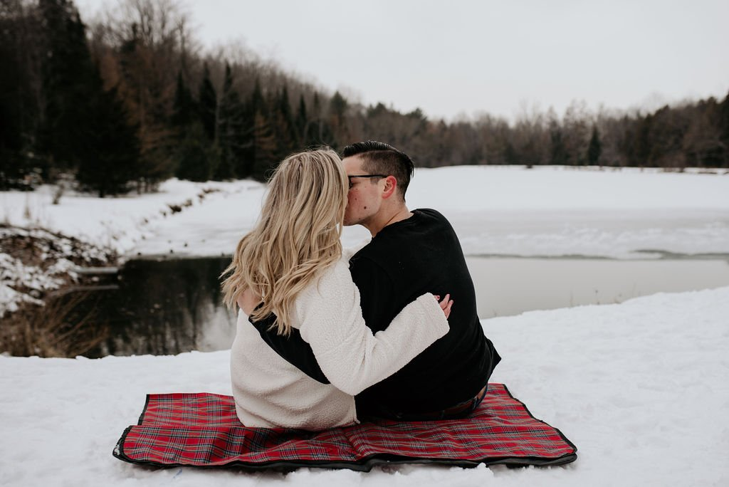 couple kissing by the lake in winter
