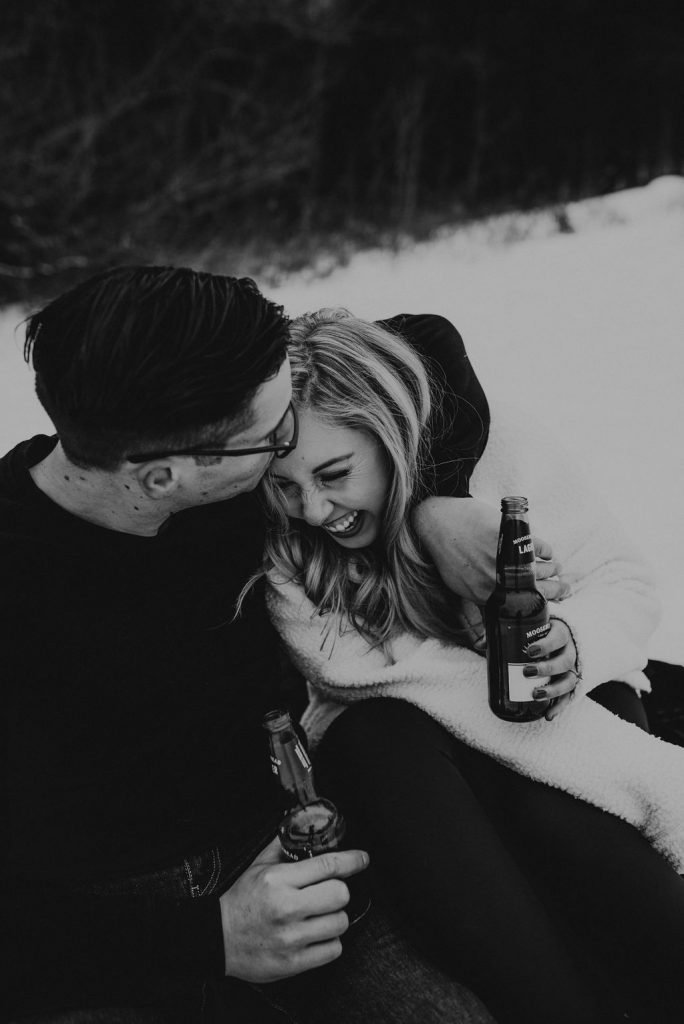 couple drinking and laughing in snow